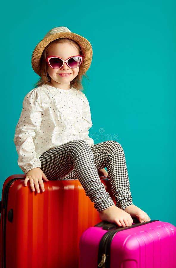 Weinig glimlachend meisje in strohoed en zonnebril die op koffers, portret zitten die van mooi kind op een reis gaan royalty-vrije stock foto's