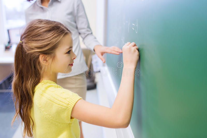 Weinig glimlachend schoolmeisje die op schoolbord schrijven royalty-vrije stock fotografie