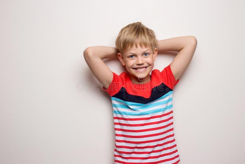 Weinig glimlachende die jongen in t-shirt op witte achtergrond wordt geïsoleerd Zij is bang royalty-vrije stock foto's