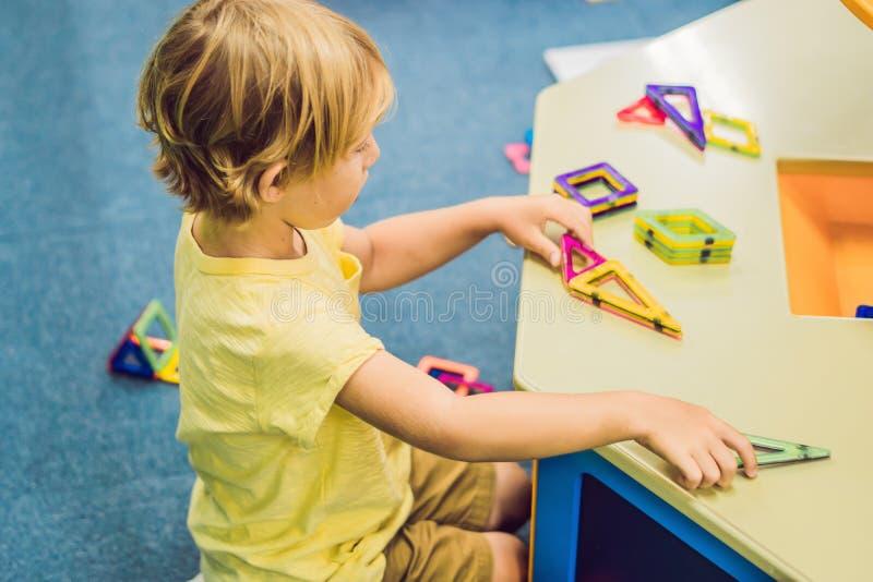 Weinig glimlachende jongen die met magnetisch aannemersstuk speelgoed spelen stock foto