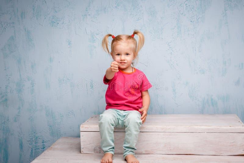 Weinig grappig blauw-eyed blonde van het meisjeskind met een kapsel twee paardestaarten op haar hoofdzitting op een roddel op de  royalty-vrije stock foto's