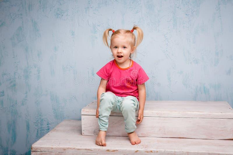 Weinig grappig blauw-eyed blonde van het meisjeskind met een kapsel twee paardestaarten op haar hoofdzitting op een roddel op de  stock foto