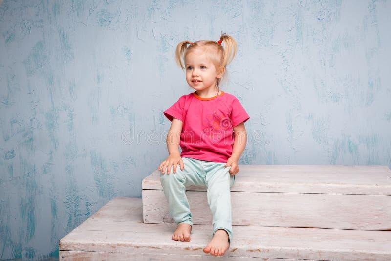 Weinig grappig blauw-eyed blonde van het meisjeskind met een kapsel twee paardestaarten op haar hoofdzitting op een roddel op de  stock afbeelding