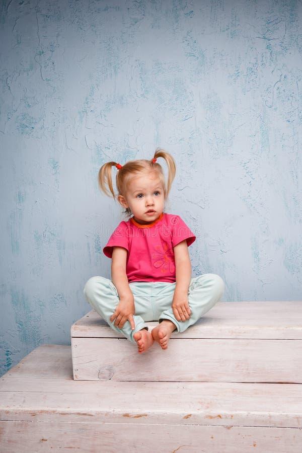 Weinig grappig blauw-eyed blonde van het meisjeskind met een kapsel twee paardestaarten op haar hoofdzitting op een roddel op de  stock afbeeldingen