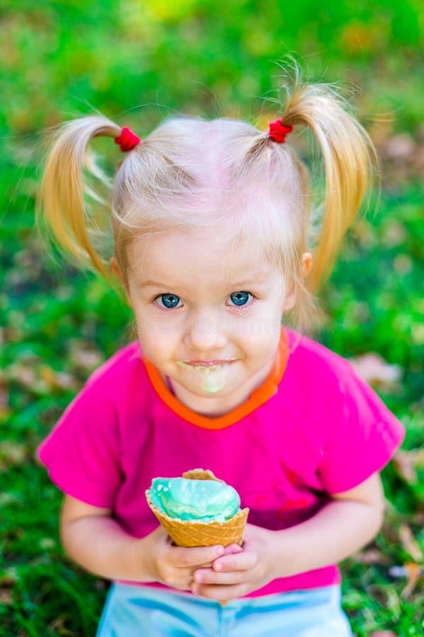 Weinig grappig Kaukasisch meisjesblonde die met blauwe ogen met twee staarten op haar hoofd een roomijs in een wafelkop eten van  stock afbeelding