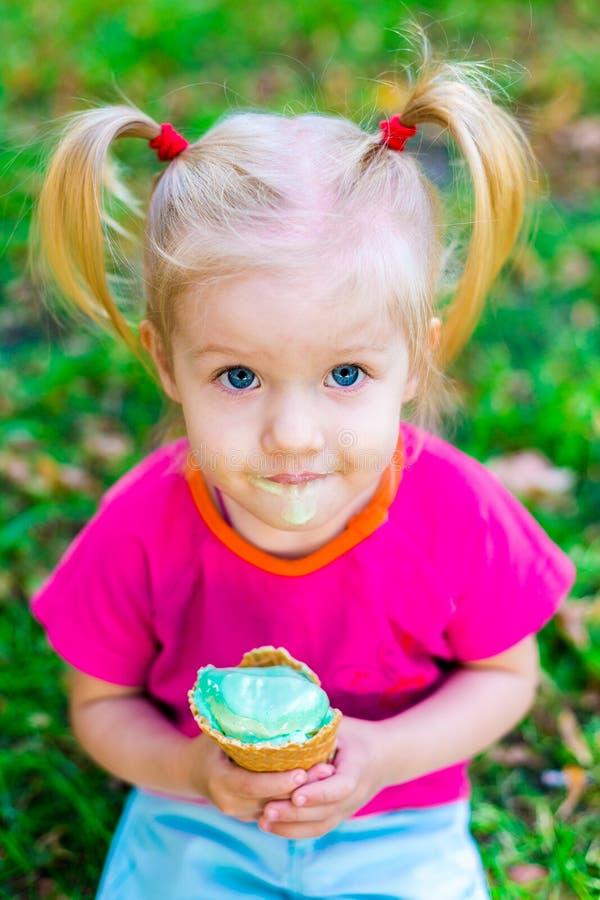 Weinig grappig Kaukasisch meisjesblonde die met blauwe ogen met twee staarten op haar hoofd een roomijs in een wafelkop eten van  royalty-vrije stock afbeeldingen