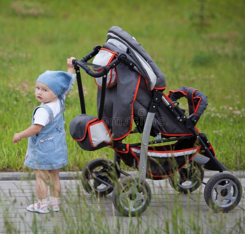 Weinig grappig meisje met kinderwagen royalty-vrije stock foto's