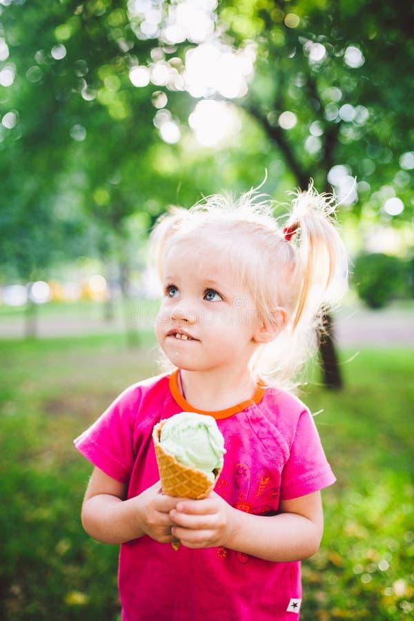 Weinig grappig meisjesblonde die zoet blauw roomijs in een wafelkop eten op een groene de zomerachtergrond in het park smeerde ha stock afbeeldingen