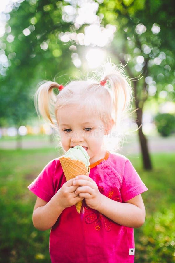 Weinig grappig meisjesblonde die zoet blauw roomijs in een wafelkop eten op een groene de zomerachtergrond in het park smeerde ha stock foto's