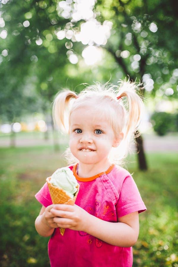 Weinig grappig meisjesblonde die zoet blauw roomijs in een wafelkop eten op een groene de zomerachtergrond in het park smeerde ha royalty-vrije stock fotografie