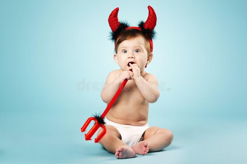 Weinig grappige baby met duivelshoornen en drietand stock foto's