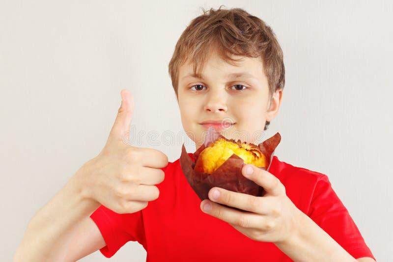 Weinig grappige jongen in een rood overhemd adviseert muffin op witte achtergrond royalty-vrije stock foto's