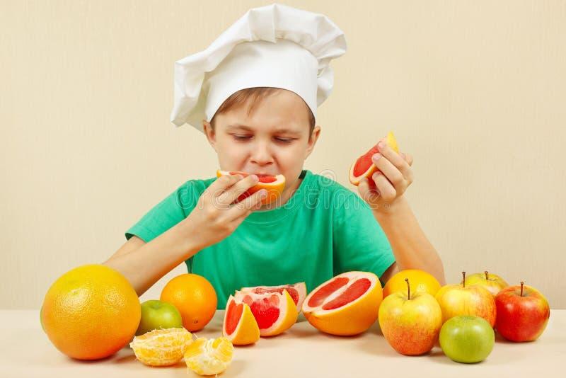 Weinig grappige jongen eet zuurrijke grapefruit bij lijst met vruchten royalty-vrije stock foto