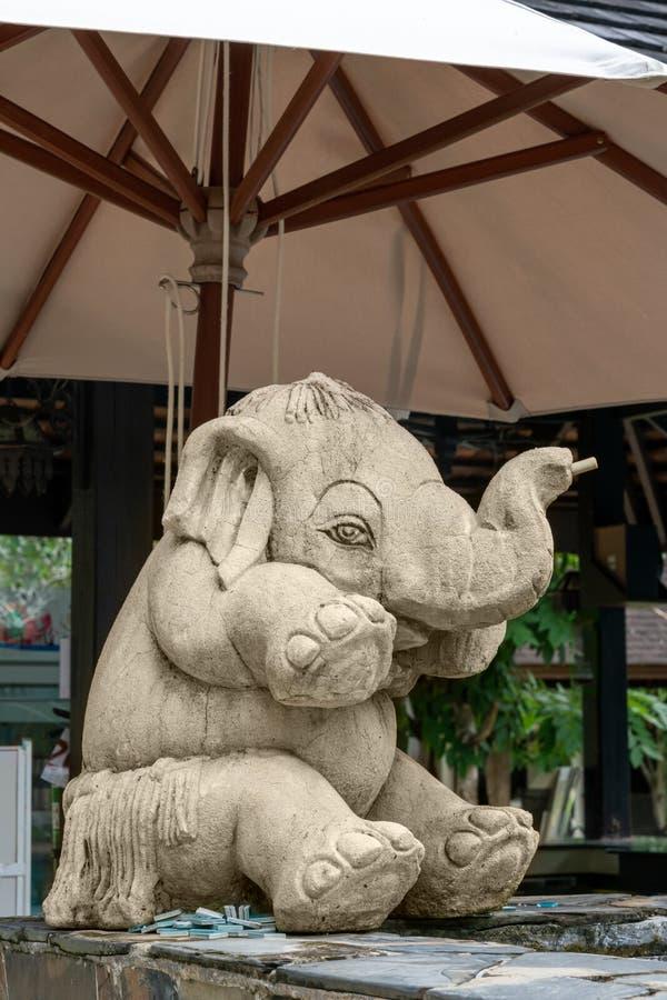 Weinig grappige olifant, beeldhouwwerk, die onder een paraplu zitten royalty-vrije stock foto's