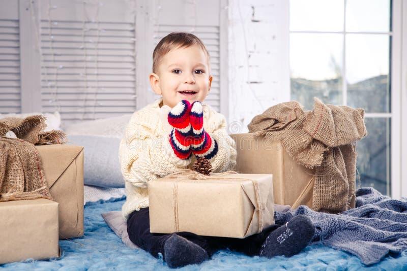 Weinig grappige speelse jongen een kind zit op een bed op Kerstmisdag met giftdozen in witte wol gebreide sweater en grote helder stock afbeeldingen