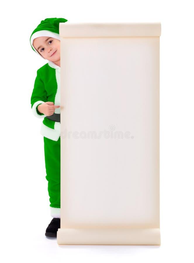 Weinig groene Santa Claus-jongen die op grote wenslijst richten stock afbeelding