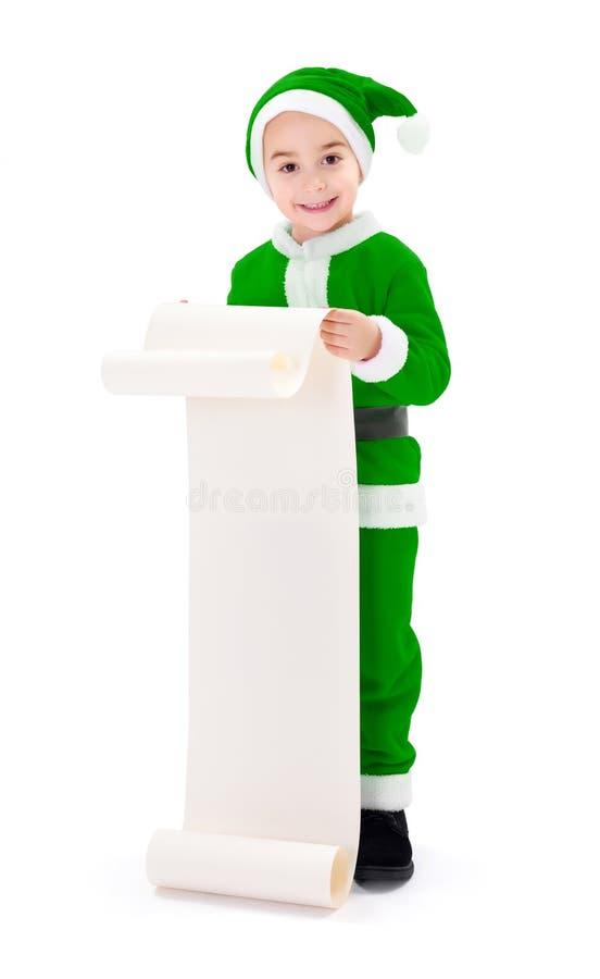 Weinig groene Santa Claus-jongen die wenslijst tonen royalty-vrije stock afbeeldingen