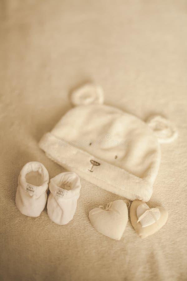 Weinig hand - gemaakte babykleren Foto van ultrasone klank pasgeboren kleren op beige wollen achtergrond geluk stock afbeelding