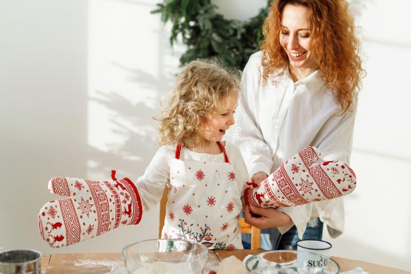 Weinig hard werkend kind draagt keukenhandschoen en schort, die haar diner van de moederkok de gaan helpen, heeft gelukkige uitdr stock afbeelding