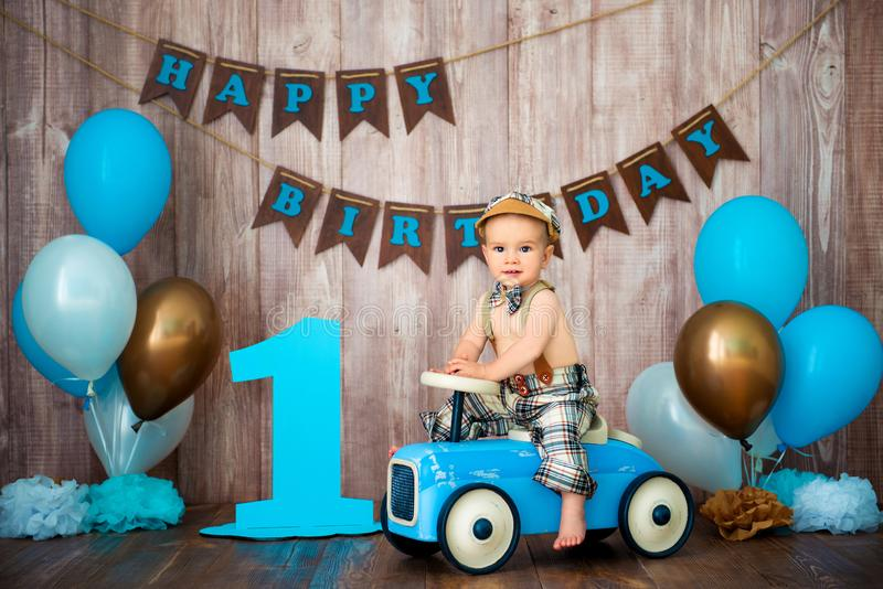 Weinig heer van het jongensjonge geitje in retro kostuum met bretels en GLB zit op een houten auto De partij van kinderen met bal stock foto's