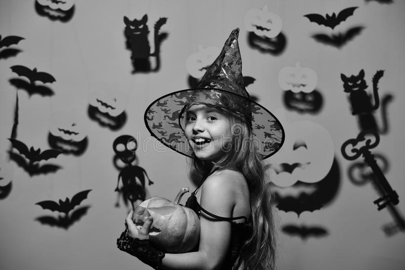 Weinig heks die zwarte hoed dragen Meisje met gelukkig gezicht op roze achtergrond met knuppels, pompoenen royalty-vrije stock afbeelding