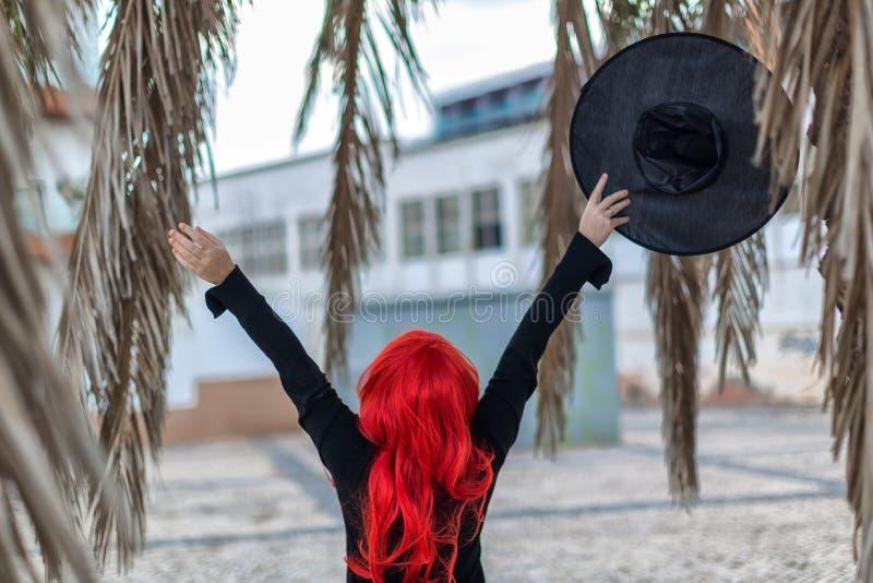Weinig heks in een zwarte kleding met rood haar houdt een hoed stock foto's