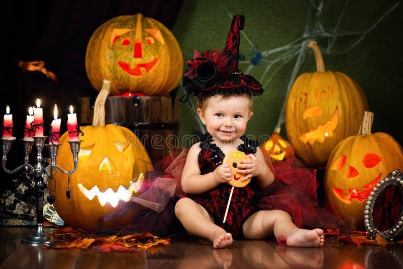 Weinig heks lacht met suikergoed in de handen onder de pompoenen en de kaarsen stock afbeelding