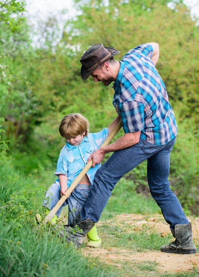 Weinig helper in tuin Leuk kind in aard die pret met cowboypapa hebben   Weinig jongen en vader met stock afbeeldingen