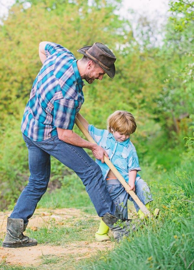 Weinig helper in tuin Leuk kind in aard die pret met cowboypapa hebben Vind schatten Weinig jongen en vader met royalty-vrije stock foto's