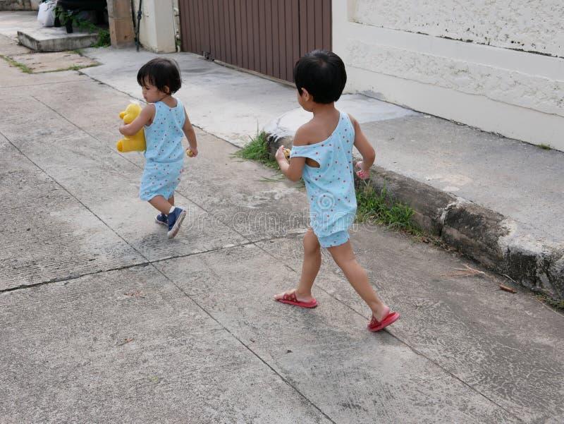Weinig het Aziatische babymeisje juiste lopen na haar babyzuster en het genieten van begeleidend haar zuster terwijl het leren en stock afbeeldingen