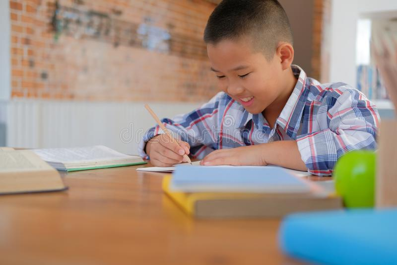 weinig het Aziatische de schooljongen van de jong geitjejongen het schrijven trekken op notitieboekje Chil royalty-vrije stock afbeelding