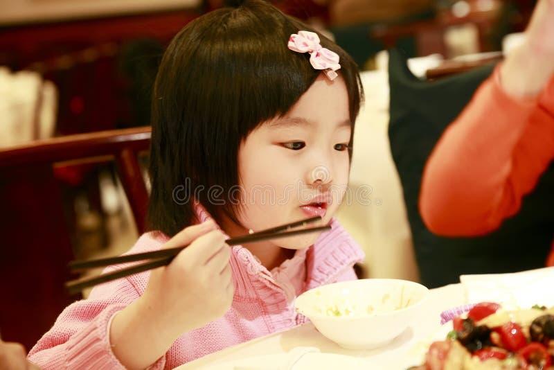 Weinig het Aziatische meisje eten stock afbeeldingen