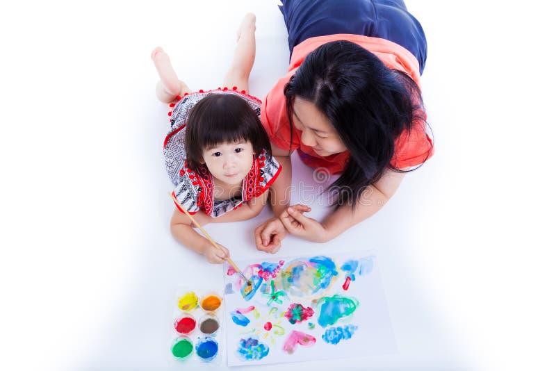 Weinig het Aziatische (Thaise) meisje schilderen met haar dichtbij langs moeder, op wh royalty-vrije stock foto's