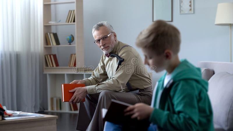 Weinig het document van de jongenslezing boek, zijn grootvader het letten op met trots, onderwijs royalty-vrije stock afbeelding