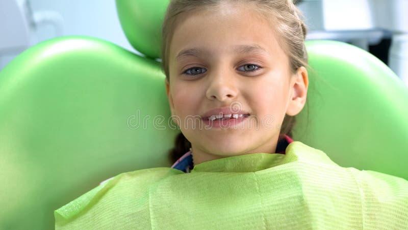 Weinig het glimlachen meisjeszitting als tandartsvoorzitter na procedure, mondelinge gezondheidszorg royalty-vrije stock afbeelding