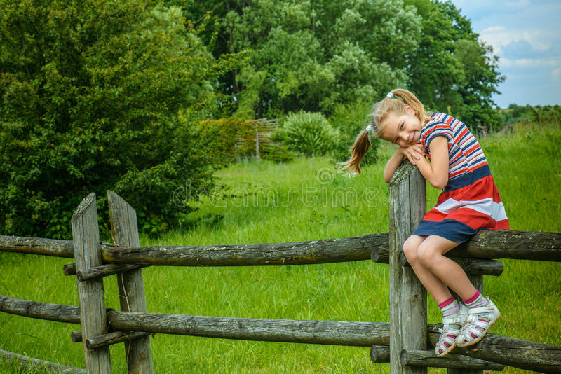 Weinig het glimlachen meisjeszitting op houten omheining royalty-vrije stock foto's