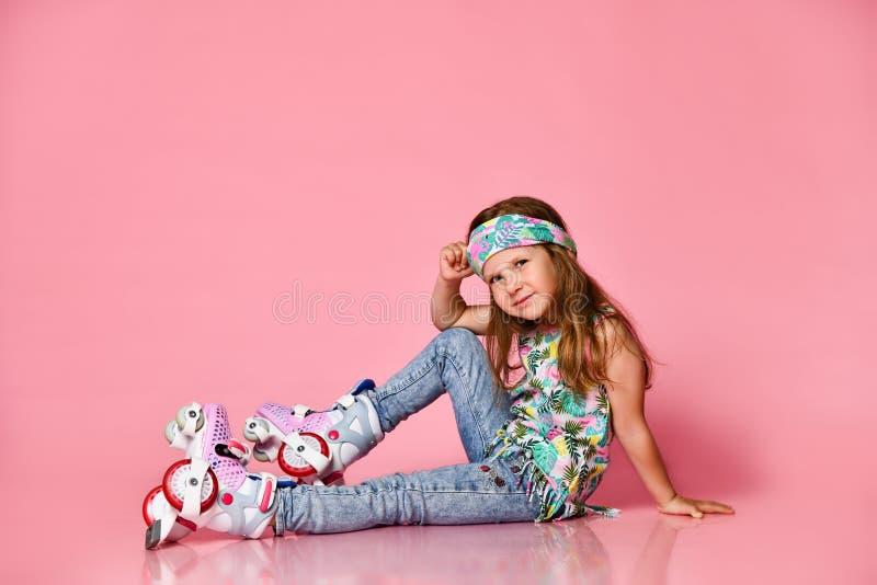 Weinig het kindzitting van het baby blonde haar met rolschaatsen in een wit overhemd en hairband gelukkige glimlach op een roze s royalty-vrije stock afbeelding
