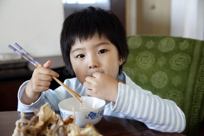 Weinig het leuke Aziatische meisje eten royalty-vrije stock afbeeldingen