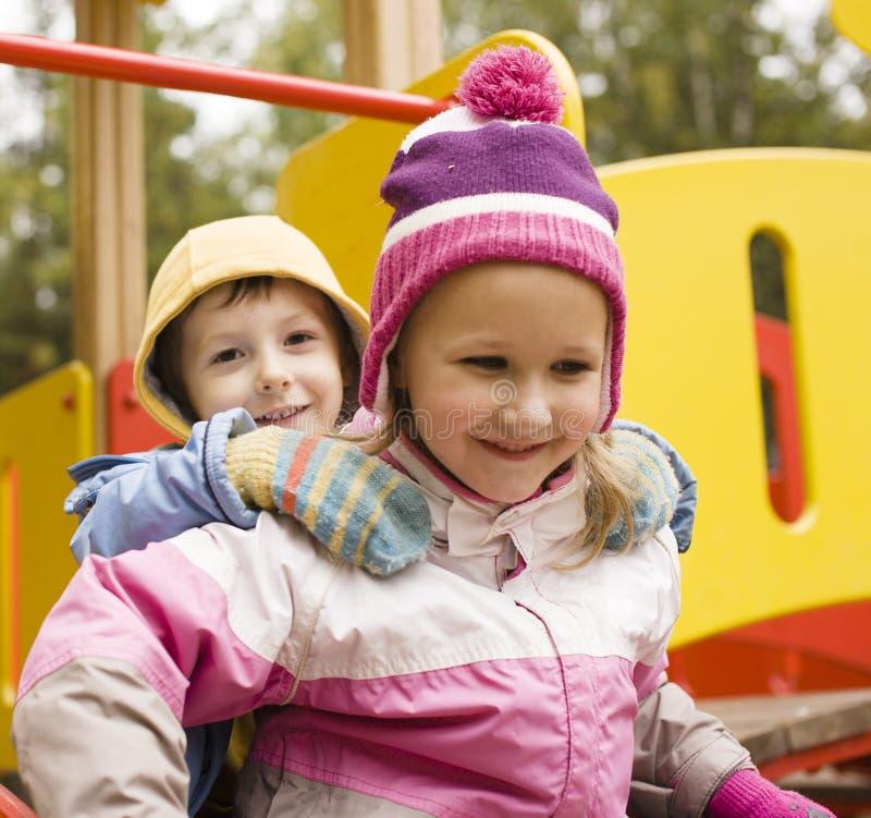 Weinig het leuke jongen en meisjes spelen buiten op speelplaats royalty-vrije stock afbeeldingen