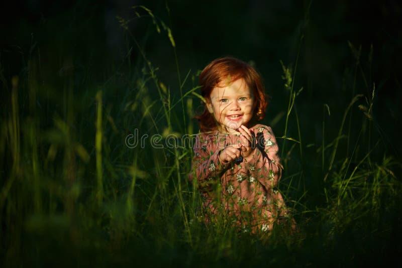 Weinig het mooie roodharige het meisje van de meisjesbaby glimlachen, die in t zitten royalty-vrije stock foto's