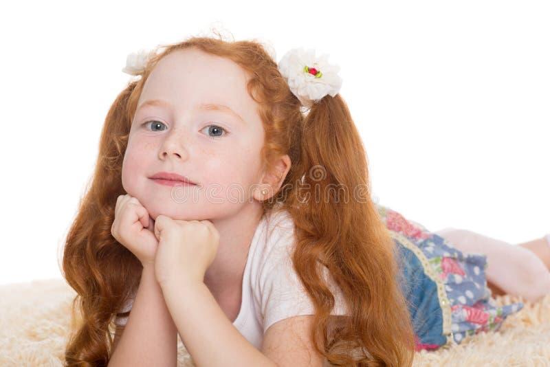 Weinig het rode haired meisje liggen stock afbeelding