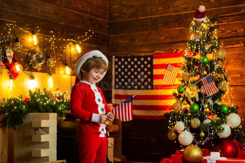 Weinig hoed en kostuum die van jongenssanta pret hebben Amerikaans traditiesconcept De peuter viert Kerstmis Ware Amerikaan stock fotografie