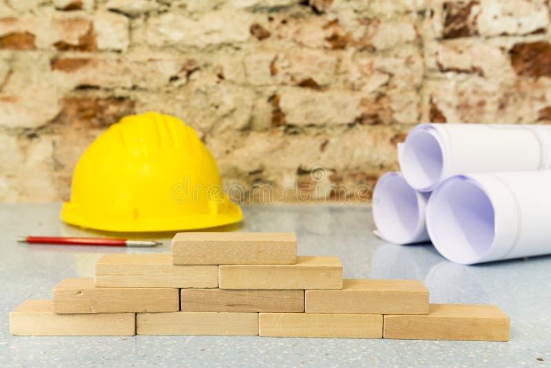 Weinig houten blokken, veiligheidshelm en tekeningenproject op bakstenen muurachtergrond royalty-vrije stock foto's