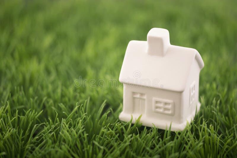 Weinig huis op groen gras stock afbeeldingen