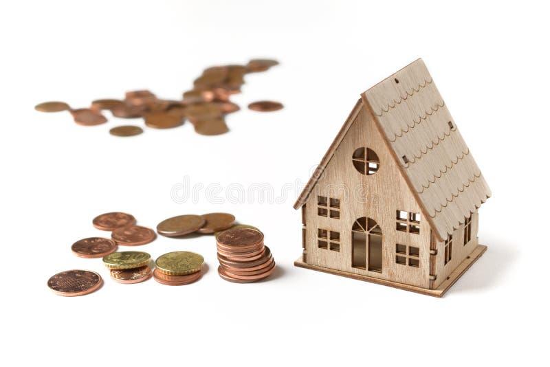 Weinig huismodel op een witte achtergrond met muntstukken naast stock afbeelding