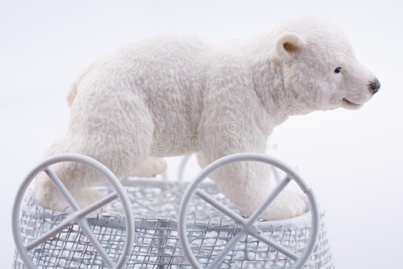 Weinig ijsbeercijfer in een stuk speelgoed kinderwagen stock fotografie