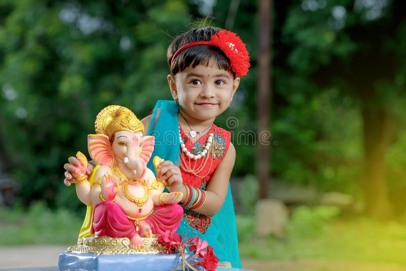 Weinig Indisch meisjeskind met Lord ganesha en het bidden, Indisch ganeshfestival stock foto's