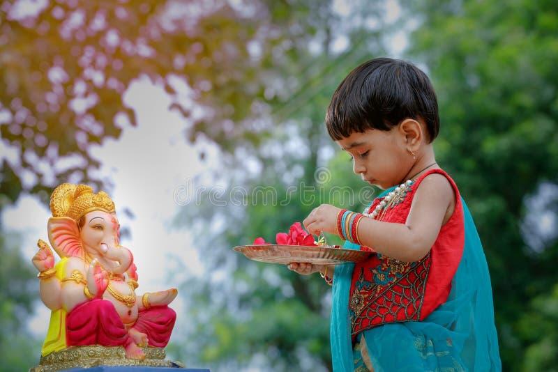 Weinig Indisch meisjeskind met Lord ganesha en het bidden, Indisch ganeshfestival stock foto