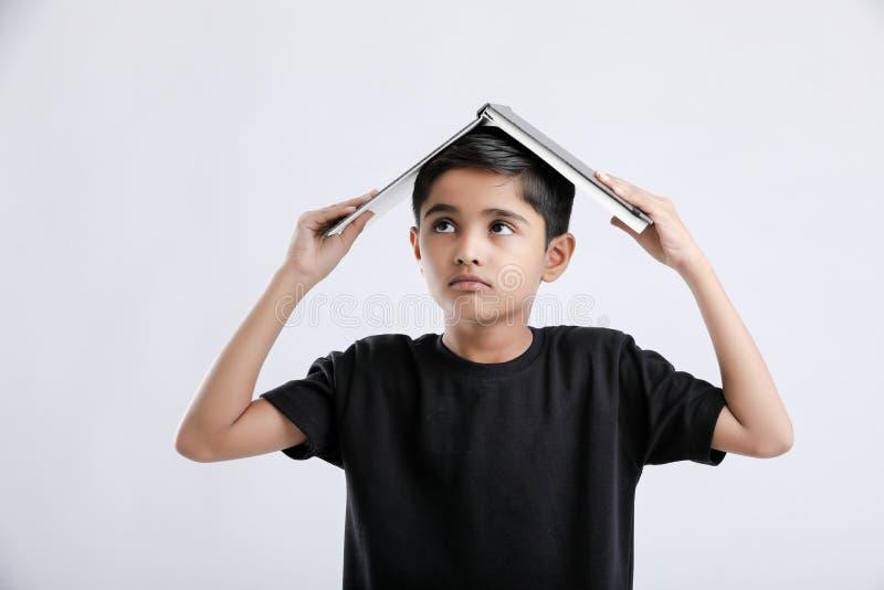 weinig Indische/Aziatische jongen met boek op hoofd en ernstig het denken stock fotografie