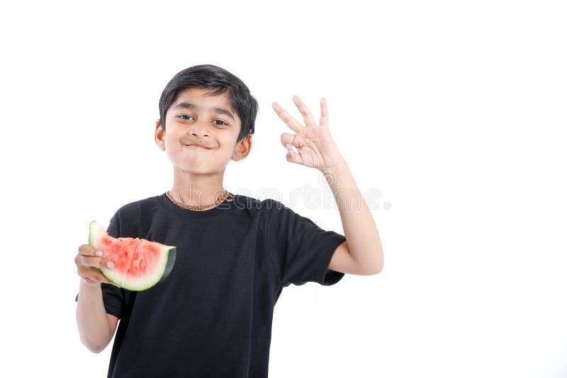 weinig Indische jongen die watermeloen met veelvoudige uitdrukkingen eten stock afbeelding